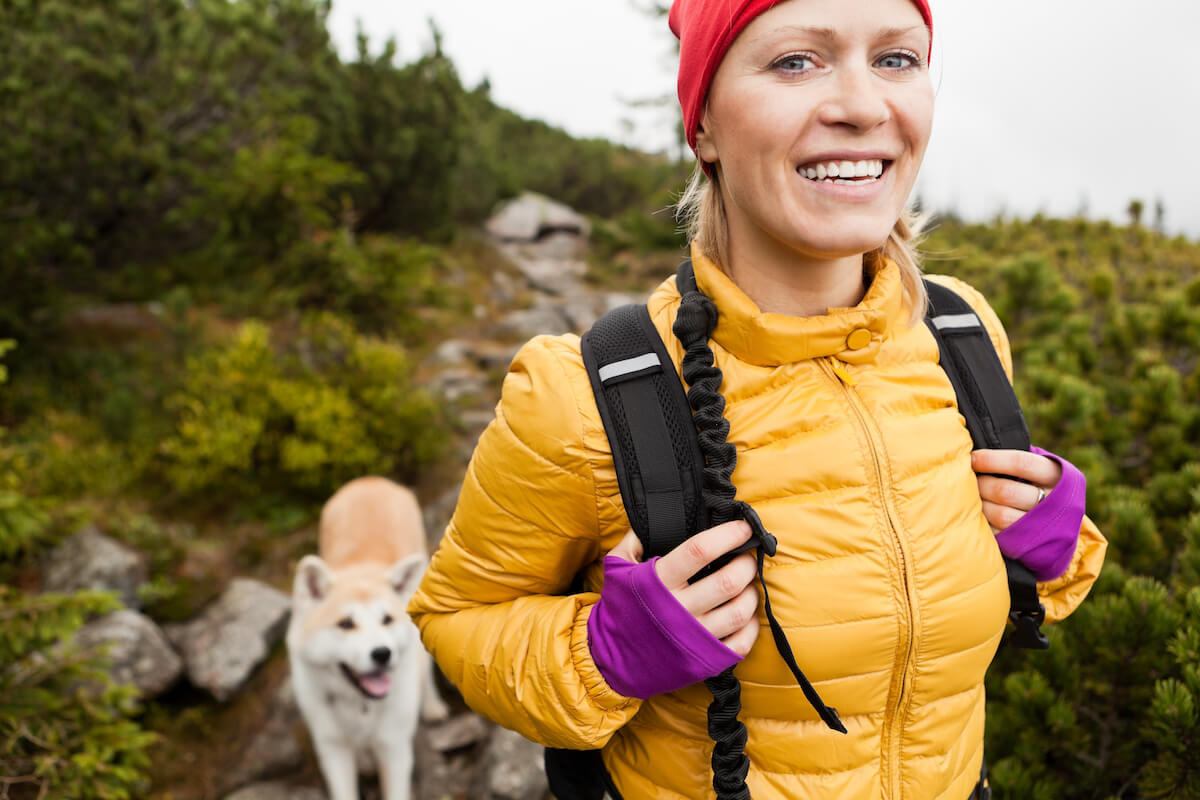 Frau mit Hund beim Hiken ©shutterstock.com/Blazej Lyjak -https://www.shutterstock.com/de/image-photo/happy-smiling-woman-hiking-mountains-akita-115418296