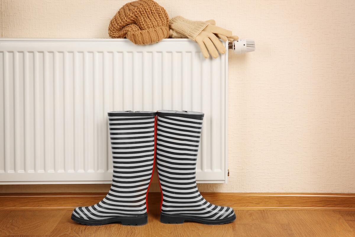 Heizung mit Gummistiefeln, Haube und Handschuhen. ©shutterstock.com/Africa Studio - https://www.shutterstock.com/de/image-photo/heating-radiator-rubber-boots-warm-clothes-531860683?src=S0aBcGcBNkK4OmOmAXzXTg-1-23