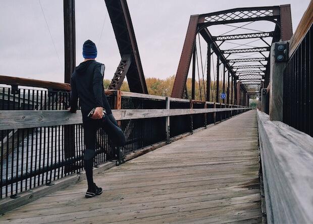 Läufer auf einer Brücke beim dehnen ©pexels.com - https://www.pexels.com/photo/adult-architecture-athlete-boardwalk-221210/