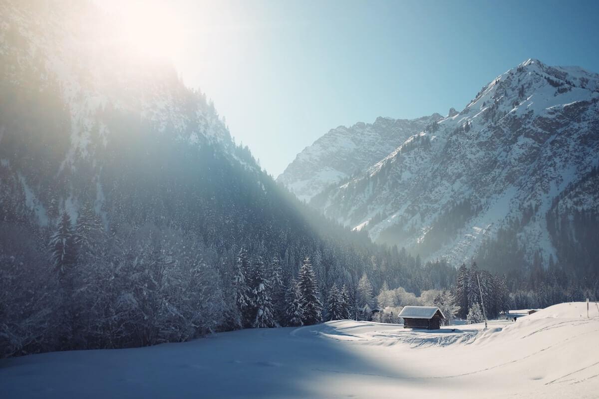 Schneelandschaft mit Bergen und Hütte. @unsplash