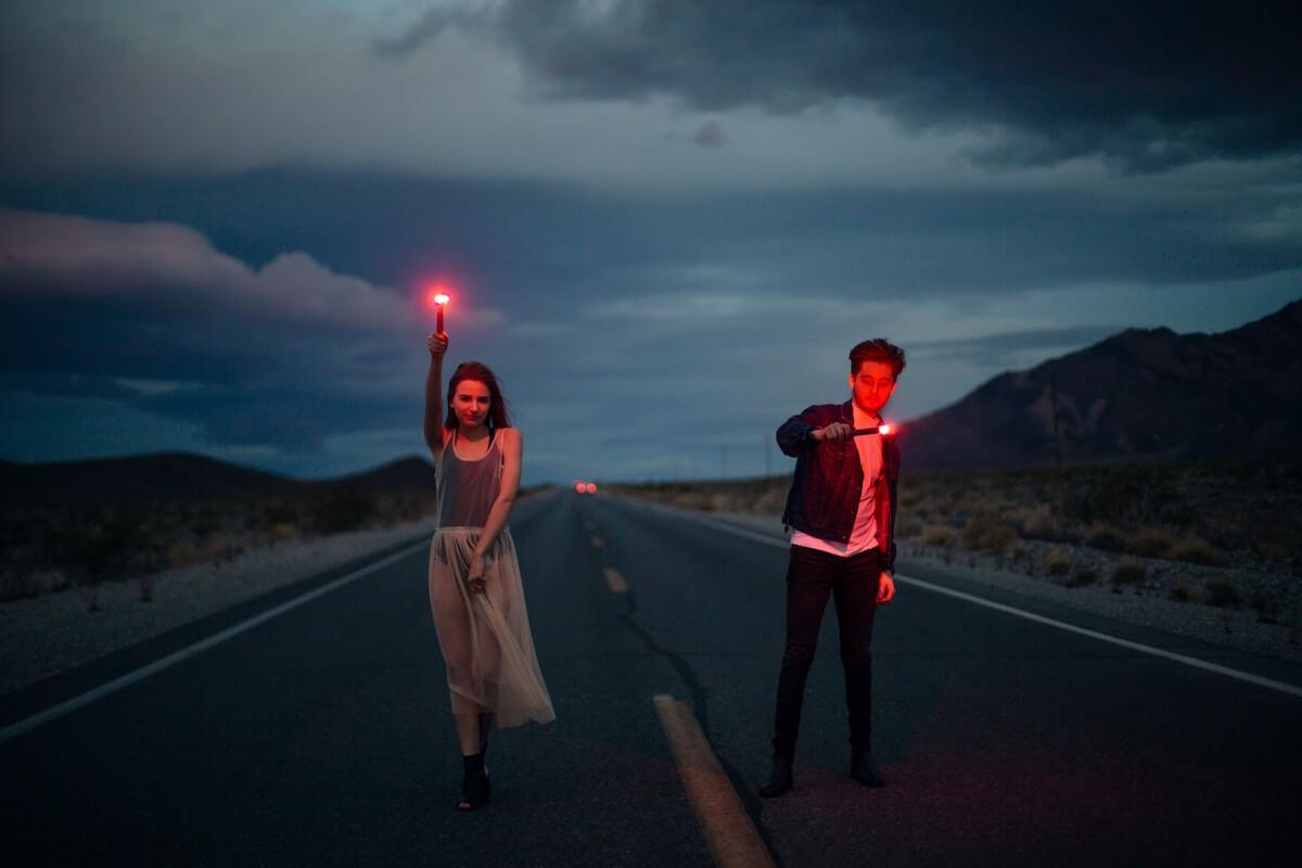 Mann und Frau auf der Straße mit Leuchtkerzen. @unsplash