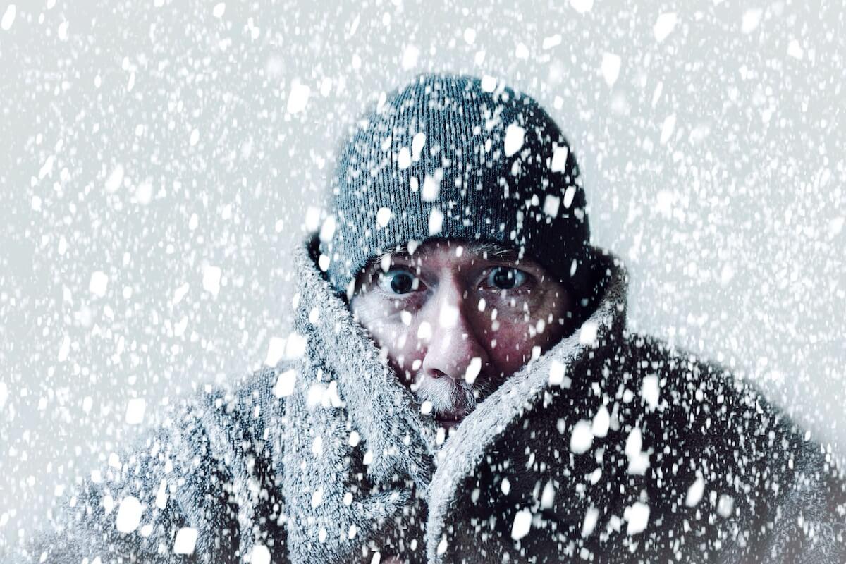 Winterszene mit älterem Mann, dem kalt ist. @shutterstock.com/Pepgooner