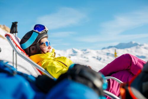 Skifahrerin sonnt sich im Liegestuhl neben der Piste©In der Sonne bräunen. ©Sergey Mironov