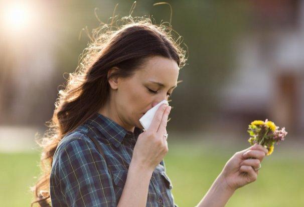 Frau beim Schneuzen mit Blumen in der Hand. @shutterstock